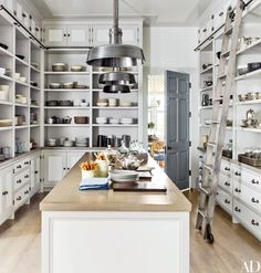 In the pantry of a Bridgehampton, New York, home designed by Steven Gambrel, a white-oak ladder by Putnam Rolling Ladder Co. makes the tall shelves easily accessible; polished-nickel pendant lamps by Hudson Valley Lighting illuminate the space.