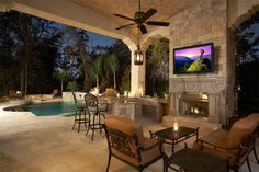 This #backyard home theater has a TV mounted over the fireplace and ample seating. The covered patio protects you from the elements, making this setup work well in all kinds of weather.