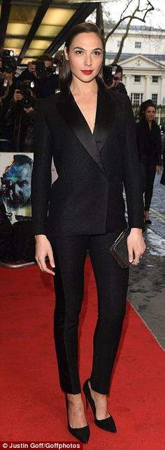 Suited and booted: Gal Gardot opted to show her co-stars (including Kevin Costner - above) how it¿s done in a fitted black trouser suit as she attended the London premiere of her new film, Criminal on Thursday evening