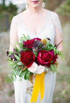 Tomasina and James threw a romantic, west coast-chic wedding in Carmel, California, and worked with a bold color palette that extended into their big day flowers. The bride carried a bouquet of burgundy peonies, blush roses, and plenty of greenery, created by Sweet Marie Designs.
