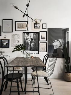 gorgeous black and white gallery wall behind dining table, wooden plank dining table, bertoia wire dining chairs with fur seat, mid century light fixture