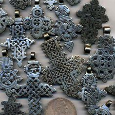Ethiopia | Coptic Crosses   Historically from about 400 AD Ethiopian Christians have cast, or carved from large silver coins such as the Maria Theresa Thaler, ornate looped crosses with styles distinctive to each highland town. || These hand carved nickel pieces are still made and worn today. | Mixed designs as shown, $9 Each; $35 / 5 different; $60 / 10 different