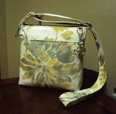 """Etsy (SewIngeniousDesigns)  Subtle Elegance occasional purse. Very limited quantity of this floral pattern & textured weave. 9.5"""" W x 9"""" T on a 4"""" protective nylon base. Handle adjusts to a 23"""" drop from the shoulder & a convenient key fob is attached. Top full-width zipper is accented with a sparkly beaded tassel. Roomy & beautiful purse interior has large zipper pocket & 2 nice-sized drop pockets. Split pocket design on front for your phone, keys or other must-haves w/ a mag-snap closure."""