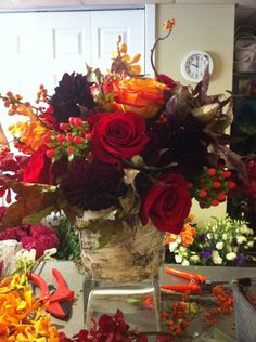 Textured fall arrangement in reds, burgundies and orange in a birch bark container.  Flowers by Petal's Edge Floral Design.