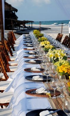 A beautiful beachside #wedding reception table setup with #floral arrangements in shades of #yellow at Viceroy Riviera Maya