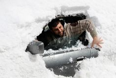 A man removes snow covering his car after a heavy snowstorm in the Aley area of eastern Lebanon, on March 2, 2012. (Reuters/ Mohamed Azakir)