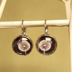 Pusteblumen fürs Ohr. Auf schwarzem Hintergrund in silberfarbener Fassung