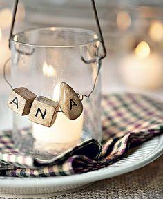 O potinho com vela tem letras de madeira, que marcam o lugar do convidado na mesa