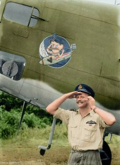 Wing Commander W.G. Leer of the R.A.A.F. poses in front of his caricature, Milne Bay, Papua New Guinea, 1943. (A Beaufort)
