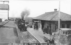 Geuda Springs Depot, Kansas View (identified with the caption Arrived on Time - Geuda Springs, KS) of a steam-powered locomotive pulling a train into the Geuda Springs Depot in Sumner County, Kansas. Also visible are a grain elevator, box cars, baggage carts, the depot building, men standing on the depot platform, and a large, horse-drawn carriage. Date: Between 1880 and 1899