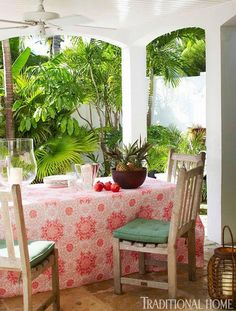 """Set with the tropical bounty of pomegranates and pineapples, a table is covered by one of the versatile, washable quilts India designed for HSN."" Hibiscus Hill, the Bahamian home of India Hicks, David Flint Wood, and their children. Photography by Colleen Duffley. ""Model, Designer India Hicks' Home in the Bahamas"" written by Rebecca Christian. Traditional Home."