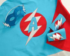 This bespoke superhero cape, mask and cuffs set is a made-to-order item featuring the initial of your little superhero in the logo. The matching