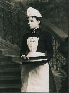 """""""1900年代前半、ヴィクトリア朝からエドワード朝にかけての時代に撮影されたメイドの写真。 トレーを手に郵便物を運んでいる。"""""""