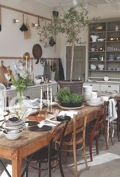 A worn wooden table, mismatched chairs, and greens everywhere: the ultimate bohemian kitchen/dining space