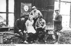 Nazi Party members gathering before an election poster featuring Adolf Hitler, summer of 1932
