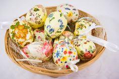 Groep kleurrijke Pasen eieren versierd met bloemen gemaakt door decoupage techniek in een mand op li Stockfoto