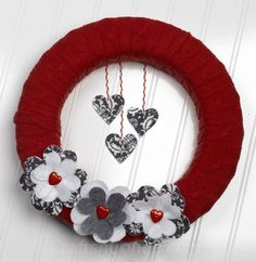 Repurposed Sweater Wreath using grey and white flowers and heart buttons to finish.
