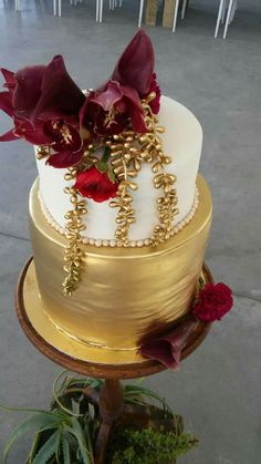 Gold wedding cake with red floral decor