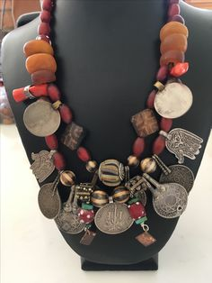 designed by AnnsEthnicJewellery old Moroccan coins. Two Moroccan silver hamsas. six old real  amber. cornaline D'Aleppo Venetion. Pumtek beads Burma. Jatim glass. New coral  wrapped in sterling silver and Yemen old  bobbly beads rare. silver clasp