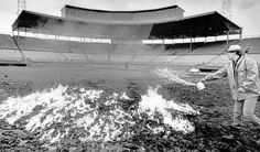 Efforts to dry the playing surface at Rosenblatt Stadium took interesting forms over the years. On several occasions, the infield dirt was burned with gasoline. Here, Terry Cuevas spreads mixture of solvent and gasoline. THE WORLD-HERALD