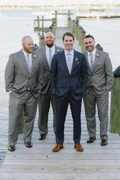 Dark blue suit for the groom and grey suits for the groomsmen look so classy together.