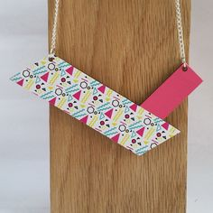 This versatile necklace is designed to be worn 2 ways. For days when you want to make more of the statement, the front of the necklace features a jazzy 80s style print print. There is a bright pop of colour with a rich pink hue. For those more understated days, the reverse of the necklace is plain wood cut into clean, simple lines to create a necklace with understated elegance. The pendant has been treated with a varnish to seal the wood. The wooden pendant hangs from a ...