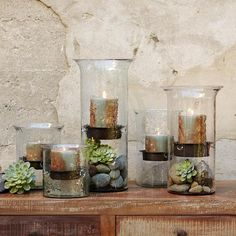 river rocks and succulents in the hurricane lamps