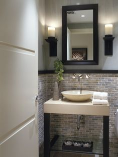 This small bathroom coveres the bottom half of the wall in a natural mosaic tile.  Looks great with the chair rail. Basement bathroom idea!