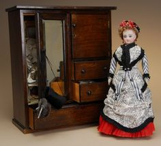 """German Fashion Lady with Wardrobe  Sign In to see what this sold for  Ca. 1890, bisque socket head on shoulder plate incised 2 on head, blue glass eyes, finely painted brows and lashes, closed mouth, pierced ears, original brown mohair wig and gusseted French fashion kid body. Wearing black and white silk gown with red skirt, original blue leather shoes. Lot includes a wooden armoire filled with homemade clothes, two original chemises and underwear, and accessories. 14.5"""" H. Very Good…"""