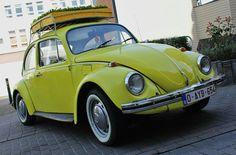 Yellow VW Beetle with roof rack filled with flowers.