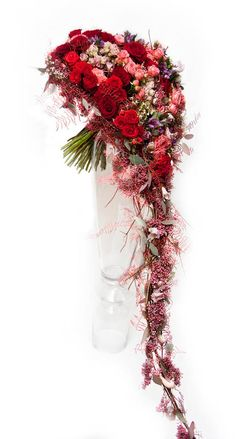 Heart shaped trailing bridal bouquet with red roses and soft fern.  Artist: Roman Steinhauer