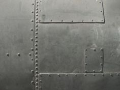 """""""rivet wall"""" in a more random pattern. An effect like this could be achieved with plywood panels and faux rivets (domed wood plugs), and we could paint it the same color as  adjacent walls"""