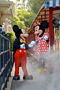 Mickey Mouse holding Minnie Mouse's hand as she steps down from a Disney Railroad train