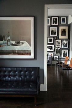 grey walls, black leathered sofa, decorated with vintage photos and a touch of khaki accent
