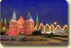 "Luebeck Holsten Gate at Christmas "" Christmas Fairy Tale Forest For 30 years Lübeck's Fairy Tale Forest has been a festive attraction. 500 illuminated fir-trees and 21 stalls beautifully recreate tales of the Brothers Grimm."""