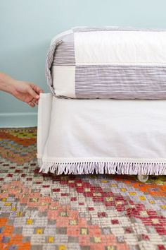 Instead of settling on a standard (read: boring) skirt for your bed frame, jazz things up with your own DIY patterned or fringed fabric.