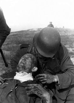 A seriously wounded German soldier is tended to by a comrade during the opening stages of Operation Barbarossa, the German invasion of the Soviet Union. Smolensk Oblast, Russia, Soviet Union. July 1941.