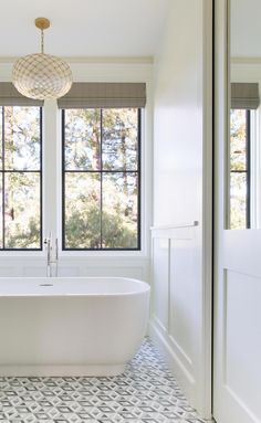 The freestanding contemporary tub is the Laura Kirar design from Kallista with a Waterworks freestanding faucet in nickel. The hanging light is Serena & Lily's Capiz Scalloped Chandelier. The sliding door with a mirrored top panel leads to the WC. #BathroomRemodel