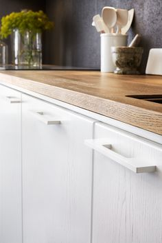 White on white detail, wood grain on cabinets, rounded edges, hardware, wooden counter, matte black :: Modernt kök i vit ask - solid vit ask alt1 vy1