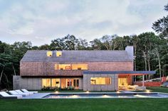 """Residential Architecture: Quail Hill House by Bates Masi Architects: """"..Approaching the house by the winding driveway, the gabled form, massive chimney, and shingled siding are all reminiscent of traditional houses on eastern Long Island. Looking closely, the shingles are, in fact, a woven screen of oak surveyors stakes, similar to those that dotted the steeply wooded lot when the clients first saw it. Similarly, the massive chimney that anchors the house to the site isn't solid at all, but…"""