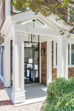 Red brick pavers frame a portico complementing a shingled home exterior lit by portico lanterns.