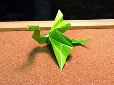 An awesome, cute green Origami dragon! Do you think it pretends to be lifeless whenever humans are present and breathes fire when left alone in the room? :)