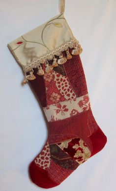 Elegant Christmas stocking with fancy trim, fabric art, crazy quilt patchwork in reds and creams with silk taffeta cuff