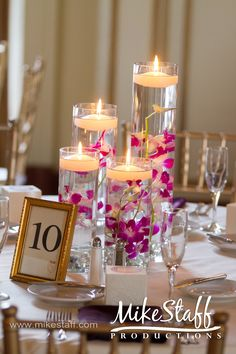 Gorgeous cylinder vase centerpieces with floating candles and flowers.