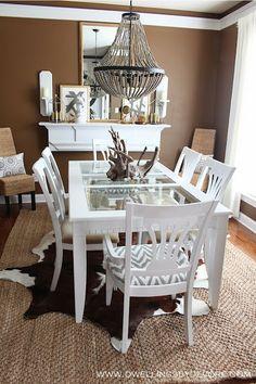 Brown Dining room with jute herringbone rug from @PlushRugs.com #layeredrugs #cowhide #beadedchandelier
