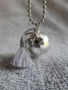 950dc173fb29 Bola de grossesse lisse argenté, avec un pompon gris en soie et une étoile,  en sautoir