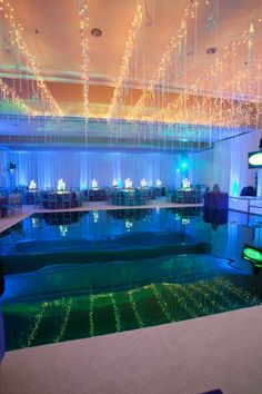 We provided all the magic including this light up stage for dancing on water! Illuminated in front of the DJ booth, a custom aqua mirrored #danceFloor was built by X-Quisite Flowers and Events Inc. for an amazing and unique effect. Guests danced all night as if there was water beneath their feet. The icicle light, crystal and ribbon ceiling treatment reflected beautifully off of the mirrored dance floor creating a natural mirror image which added depth and dimension to the #ballroom.