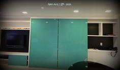 estante grande by Neo Arq com portas de correr em MDF CRistallo - Duratex. As portas camuflam a circulação para os quartos e o home office