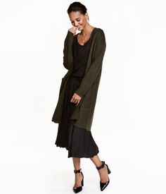 Dark green melange. Long, soft knit cardigan. Front pockets and no buttons.