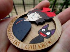Need a delivery ? Call Kiki and her black cat Jiji !  This brooch is made with two layers of laser cut and engraved wood. It is handpainted. You can